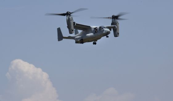 A U.S. Osprey flies back to Tribhuvan International airport in Kathmandu, Nepal, Thursday, May 14, 2015. A search continued Thursday for a U.S. Marine helicopter carrying six Marines and two Nepalese soldiers. It disappeared Tuesday while delivering aid in the country's northeast. (AP Photo/Bernat Amangue)