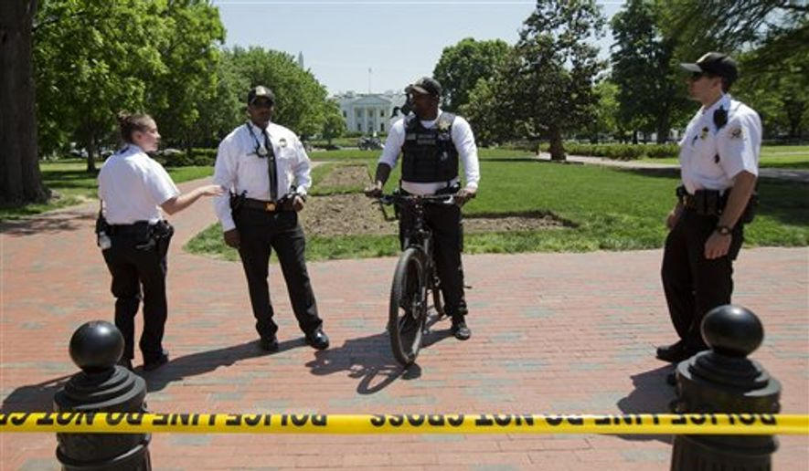 Uniformed Secret Service Police officers stand watch at Lafayette Park near the White House in Washington, Thursday, May 14, 2015, during a lockdown. A federal law enforcement official says a man has been arrested after trying to launch a drone outside the White House fence. (AP Photo/Manuel Balce Ceneta)