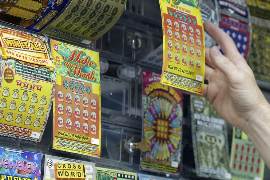 A gas station employee reaches for a lottery ticket in Little Rock, Ark., Thursday, May 14, 2015. On Thursday, a legislative committee overseeing the Arkansas lottery meets for the first time since the independent commission running the games was abolished. (AP Photo/Danny Johnston)
