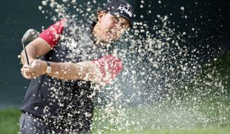 Phil Mickelson hits from a sand trap on the 15th hole during the first round of the Wells Fargo Championship golf tournament at Quail Hollow Club in Charlotte, N.C., Thursday, May 14, 2015. (AP Photo/Bob Leverone)