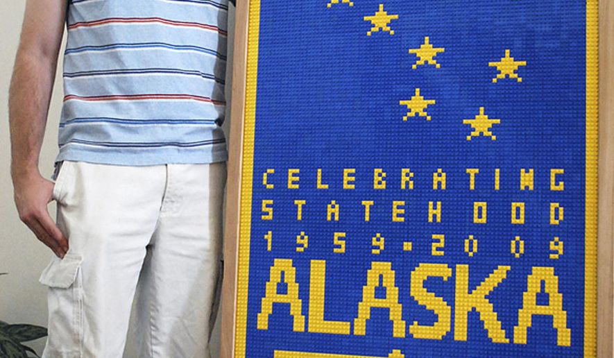 ADVANCE FOR RELEASE SATURDAY, MAY 16, 2015, AT 2:00 A.M. AKDT AND THEREAFTER - In this 2009 photo released by Susan Keltner, her husband Ty Keltner poses with a sign made of Lego in Fairbanks, Alaska. Ty Keltner is the owner of one of the largest Lego collections in Alaska. (Susan Keltner via AP)