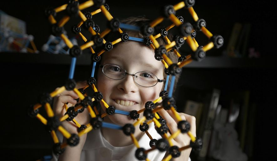 Eric Comstock, 9, looks through a model of a Adamantane CC 8 molecule he built on Monday, May 11, 2015, in Conroe, Texas. Eric began college classes at age 8 and just won the Lone Star College system Calculus 1 contest. (Melissa Phillip/Houston Chronicle via AP)