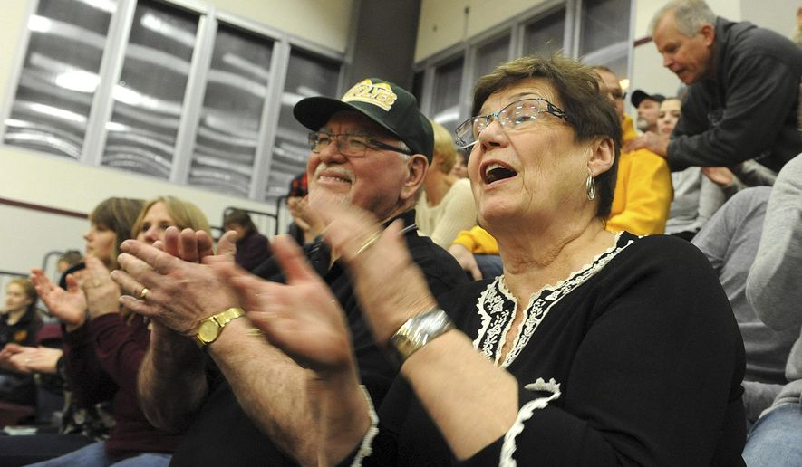 ADVANCE FOR RELEASE SATURDAY, MAY 16, 2015 THEREAFTER In this Dec. 20, 2014 photo, Keith and Lillian Lauwers cheer on the Galena Hawks and the Grace Christian Grizzlies in the 16th Annual Grace Grizzly Classic basketball Tournament at Grace Christian School in Anchorage, Alaska. One of the Lauwers grandsons, Louis Karlberg, coaches the Galena Hawks and another grandson, Tobin Karlberg, plays for the Grace Christian Grizzlies. (Bob Hallinen/Alaska Dispatch News via AP)