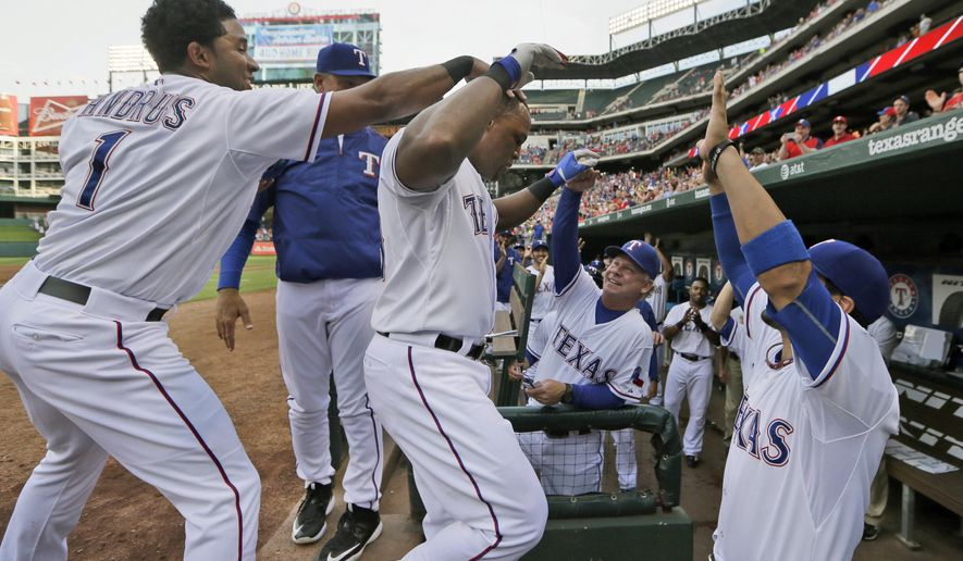 Texas Rangers Adrian Beltre, center left, celebrates his solo home run Elvis Andrus (1), Robinson Chirinos, right, and bench coach Steve Buechele during the first inning of a baseball game against the Cleveland Indians in Arlington, Texas, Friday, May 15, 2015. (AP Photo/LM Otero)