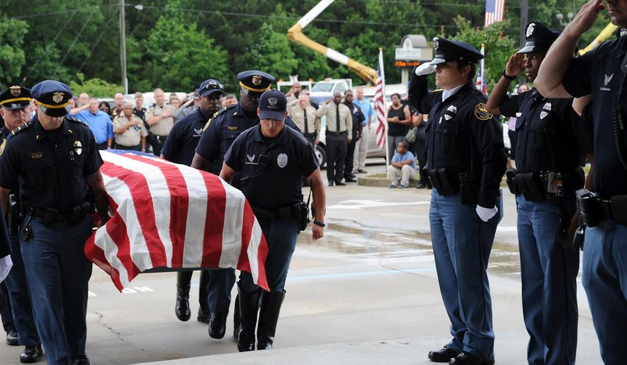 Hattiesburg Police officers carry the body of Officer Liquori Tate into West Point Baptist Church for visitation Friday, May 15, 2015, in Hattiesburg, Miss. Tate and Benjamin Deen were shot to death during a routine evening traffic stop turned violent Saturday. (Eli Baylis/The Hattiesburg American via AP)