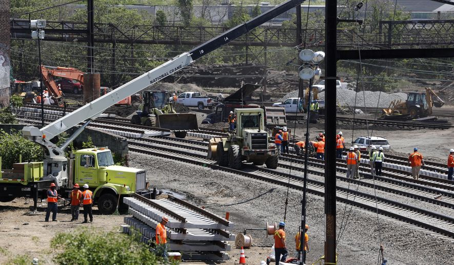 Workers labor on the site where a deadly train derailment occurred earlier in the week, Friday, May 15, 2015, in Philadelphia. Amtrak is working to restore Northeast Corridor rail service between New York City and Philadelphia. Service was suspended after a train derailed in Philadelphia on Tuesday night, killing eight passengers and injuring more than 200. (AP Photo/Julio Cortez)