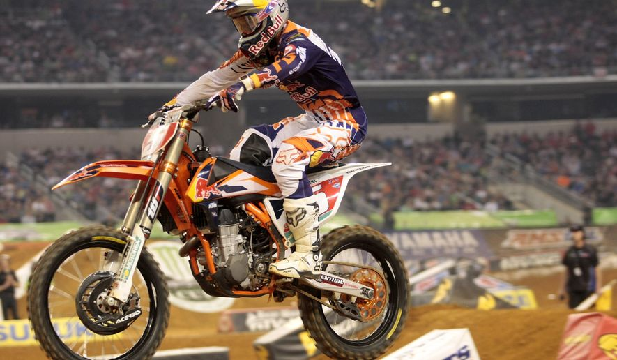 FILE - In this Feb. 14, 2015, file photo, Ryan Dungey races in one of the 450 SX Supercross heats at AT&T Stadium in Arlington, Texas. Dungey is not a flashy rider, at least by motocross standards. He is consistent, though, making him the favorite to win the outdoor title after capturing his second Supercross crown.  (Juan Guajardo/Fort Worth Star-Telegran via AP, File)