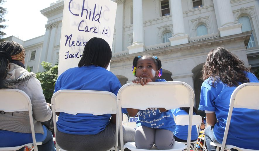 In this photo taken Wednesday May 6, 2015, Saryah Mitchell, 4, sits with her mother, Teisa, Gay, left, a rally calling for increased child care subsidies at the Capitol in Sacramento, Calif.  Democratic legislative leaders have made expanding child care for working families a top priority in their budget negotiations with Gov. Jerry Brown.(AP Photo/Rich Pedroncelli)