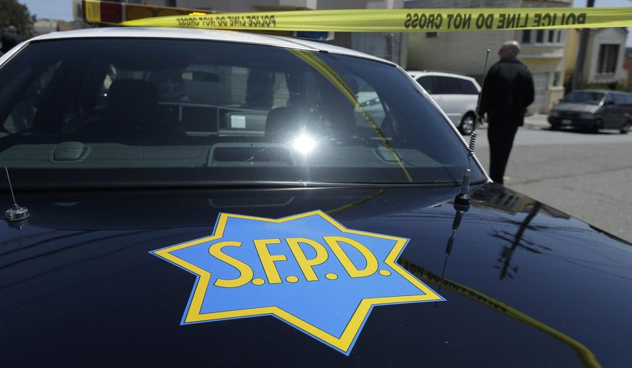 In this May 12, 2015 photo, a San Francisco Police officer walks past a patrol car parked in San Francisco. The original charges were shocking enough: six San Francisco police officers were accused of stealing from suspects living in seedy residential hotels. Then federal prosecutors released racist, homophobic and ethnically insensitive email and text messages exchanged among more than a dozen officers, prompting the San Francisco district attorney to launch a wide-ranging investigation of the police department while considering dismissing up to 3,000 criminal cases involving the officers. (AP Photo/Jeff Chiu)