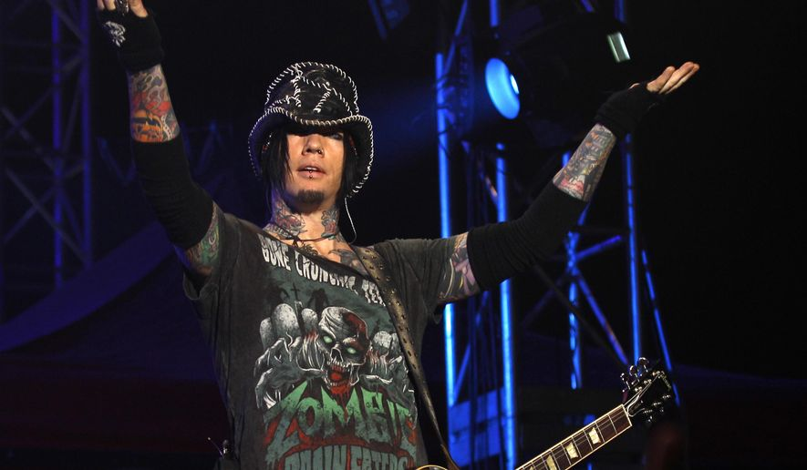 FILE - In this Dec. 7, 2012 file photo, Guns N' Roses guitarist DJ Ashba reacts to the crowd as he performs during a concert in Bangalore, India. A former Las Vegas police captain who resigned rather than be demoted for helping Ashba use the department's helicopter for an elaborate wedding proposal is poised to get his job back, have his record cleared and be paid what he would have earned since Dec. 20, 2013, when he left the department.  (AP Photo/Aijaz Rahi, File)