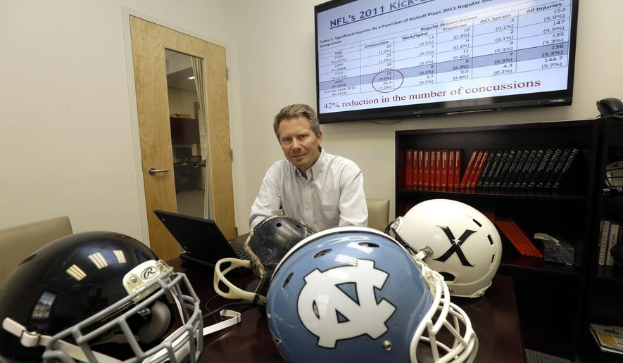 ADVANCE FOR WEEKEND EDITIONS, MAY 15-17 - In this photo taken Wednesday, May 13, 2015, Kevin Guskiewicz, professor and former chair of the Department of Exercise and Sports Medicine at the College of Arts and Sciences, is surrounded by football helmets where he conducts research on helmet sensors at the University of North Carolina in Chapel Hill, N.C. Guskiewicz noted that the NFL's decision to move up kickoffs, thereby increasing touchbacks and reducing returns, was influenced by a study that used helmets sensors on college players. (AP Photo/Gerry Broome)