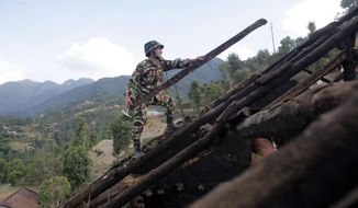 A Nepalese army soldier clears rubble from a damaged house at Lele in Lalitpur, Nepal, Thursday, May 14, 2015. On April 25, a magnitude-7.8 earthquake killed thousands of people, injured tens of thousands more and left hundreds of thousands homeless. Then, just as the country was beginning to rebuild, a magnitude-7.3 earthquake battered it again. (AP Photo/Bikram Rai)