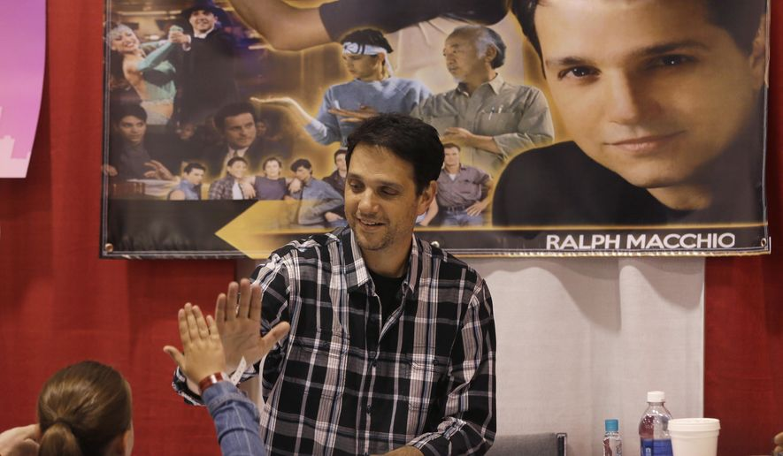 Actor Ralph Macchio, who played the Karate Kid, high-fives Sage Fauteux at the Motor City Comic Con at the Suburban Collection Showcase, Friday, May 15, 2015, in Novi, Mich. The three-day pop-culture extravaganza that gets underway Friday will welcome to the Suburban Collection Showplace in Novi dozens of celebrities from the worlds of TV, film and beyond as well as thousands of fans. Motor City Comic Con also brings in comic book and multimedia dealers who offer merchandise, including comic books, art, T-shirts and movie memorabilia. (AP Photo/Carlos Osorio)