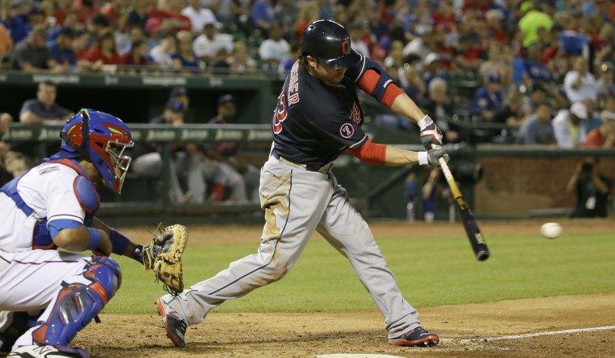 Cleveland Indians designated hitter Nick Swisher (33) hits a two run RBI single in front of Texas Rangers catcher Carlos Corporan during the fifth inning of a baseball game in Arlington, Texas, Friday, May 15, 2015. (AP Photo/LM Otero)