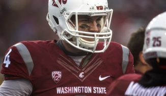 Washington State backup quarterback Luke Falk (4) smiles while waiting with teammates during a television timeout in the second quarter of an NCAA college football game against Southern California on Saturday, Nov. 1, 2014, at Martin Stadium in Pullman, Wash. Falk replaced Connor Halliday, who suffered a broken leg earlier in the game. Southern California won 44-17. (AP Photo/Dean Hare)