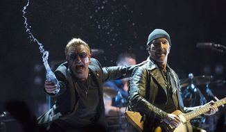 Bono, of the band U2, throws water at the crowd while the Edge watches as they perform in the band's first concert of their new world tour in Vancouver, Thursday, May, 14, 2015. (Jonathan Hayward/The Canadian Press via Associated Press) ** FILE **