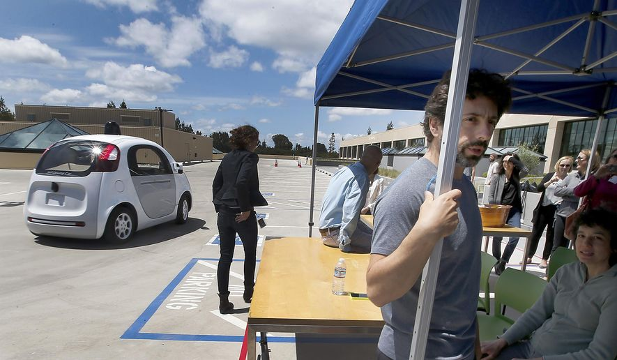 In this May 13, 2015 photo, Google co-founder Sergey Brin, right, speaks to reporters and guests about the new Google self-driving prototype car during a demonstration at the Google campus in Mountain View, Calif.  The car, which needs no gas pedal or steering wheel, will make its debut on public roads this summer. (AP Photo/Tony Avelar)
