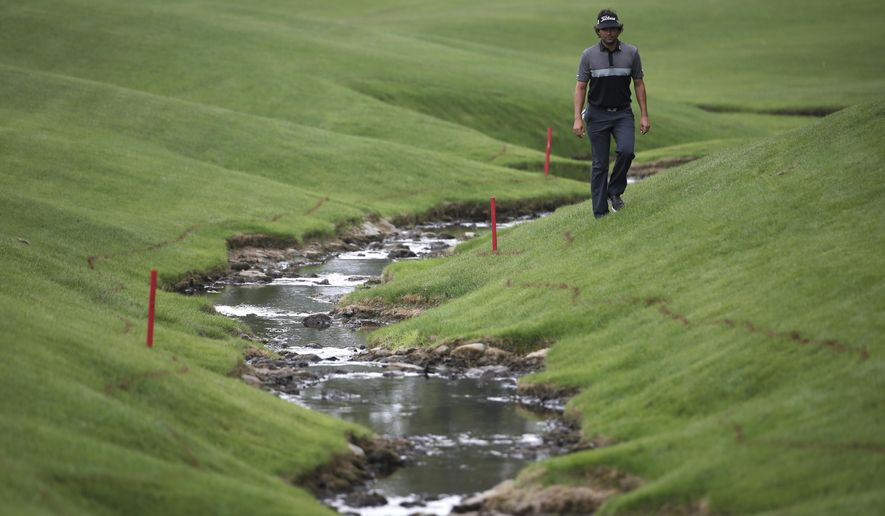 Martin Flores walks to his ball by the creek on the 18th hole during the second round of the Wells Fargo Championship golf tournament at Quail Hollow Club in Charlotte, N.C., Friday, May 15, 2015. (AP Photo/Chuck Burton)