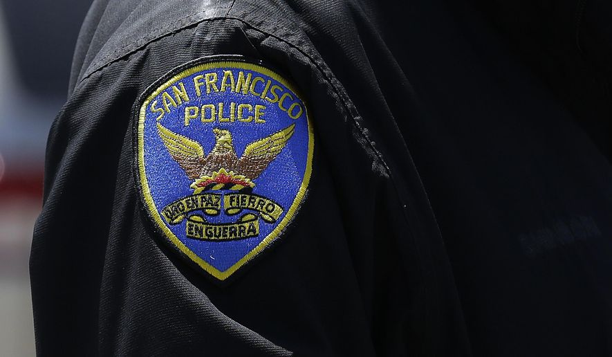 In this May 12, 2015 photo, a San Francisco Police officer stands on a street in San Francisco. (AP Photo/Jeff Chiu)