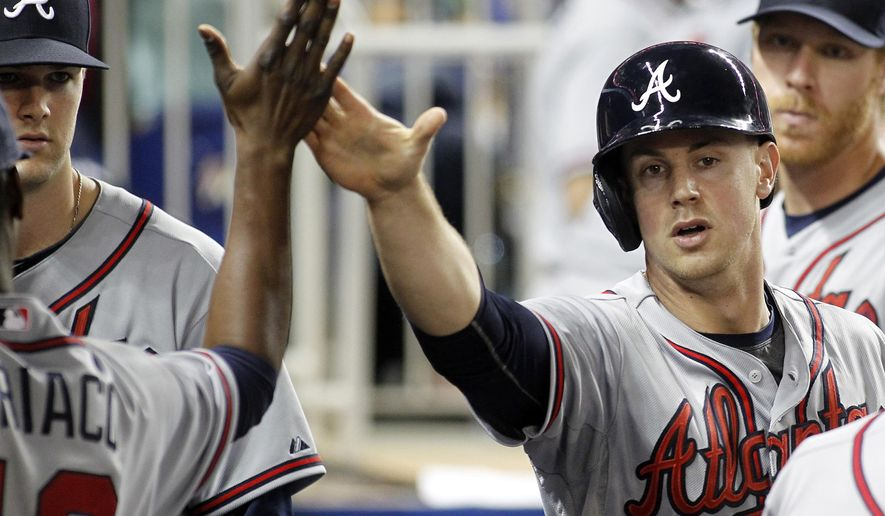 Atlanta Braves' Todd Cunningham, right, is congratulated by teammates after scoring in the fourth inning against the Miami Marlins during a baseball game in Miami, Friday, May 15, 2015. (AP Photo/Joe Skipper)