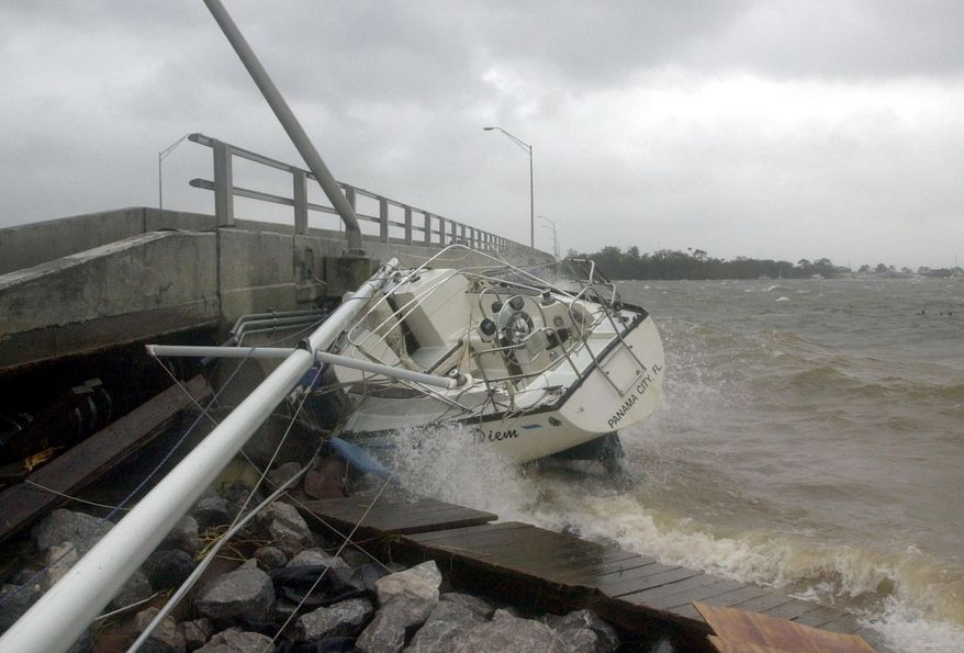 FILE - In this Sept. 16, 2004 file photo, waves crash against a sailboat lodged under a bridge in Fort Walton Beach, Fla., after Hurricane Ivan struck the gulf coast. Federal regulators believe a persistent oil spill in the Gulf of Mexico that began after a drilling platform was toppled during Hurricane Ivan in 2004 will continue for 100 years or more if left unchecked, according to estimates obtained by The Associated Press that provide new  details about the extent of the problem.  (AP Photo/John Bazemore, File)