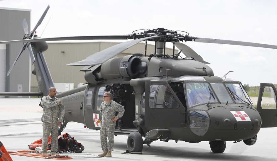 Sgt. 1st Class Bryan Scott, left, and Chief Warrant Officer Drew Zanoff, with the Colo. Army National Guard, stand with their Blackhawk helicopter, one of several craft used for firefighting which was on display at Centennial Airport in the south Denver area, Friday, May 15, 2015. Colorado will patrol its forests and grasslands with a variety of aircraft this summer, including two new wildfire-spotting aircraft, hoping to find and snuff out flames before they explode into the deadly mega-fires that have plagued the state in the past. (AP Photo/Brennan Linsley)