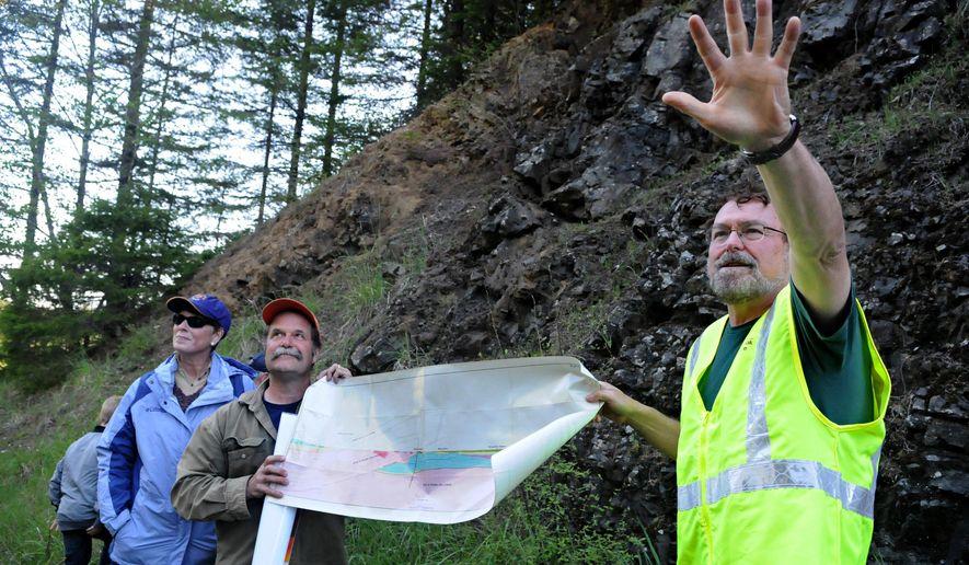 In this May 7, 2015, photo, Oregon State University emeritus geology professor Bob Lillie, right, explains the origins of volcanic rock formations on Marys Peak in Benton County, Ore. (Amanda Cowan/The Corvallis Gazette-Times via AP)