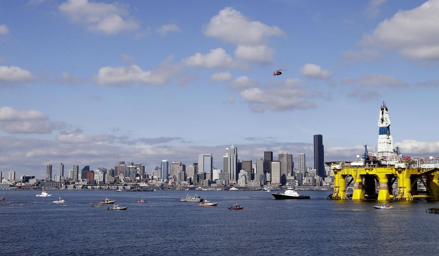 A U.S. Coast Guard helicopter flies overhead and a small flotilla of protesters in kayaks paddles behind as the oil drilling rig Polar Pioneer is towed toward a dock Thursday, May 14, 2015, in Elliott Bay in Seattle. The rig is the first of two drilling rigs Royal Dutch Shell is outfitting for oil exploration and was towed to the Port of Seattle site despite the city's warning that it lacks permits and threats by kayaking environmentalists to paddle out in protest. (AP Photo/Elaine Thompson)
