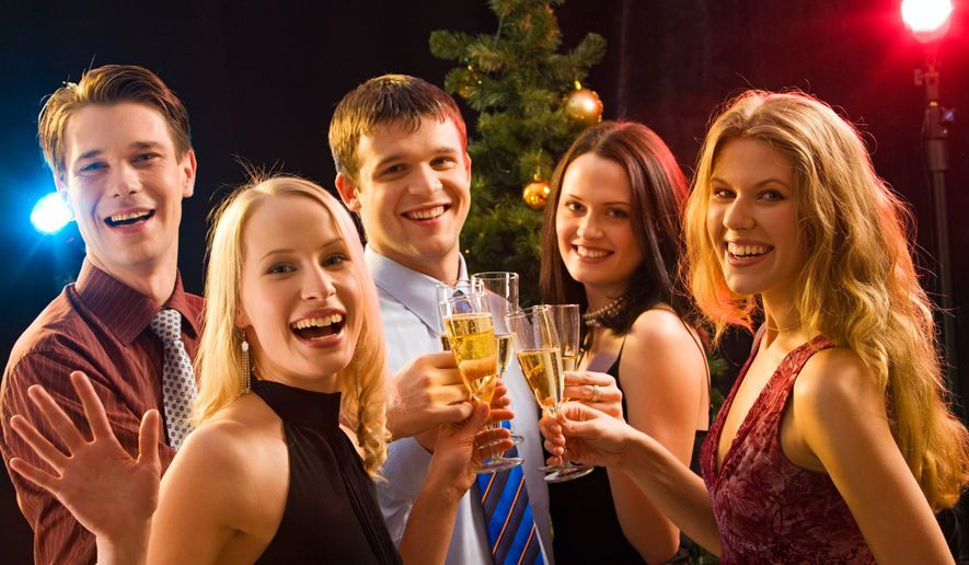 Smiling group of young people enjoying cocktails at Christmas.