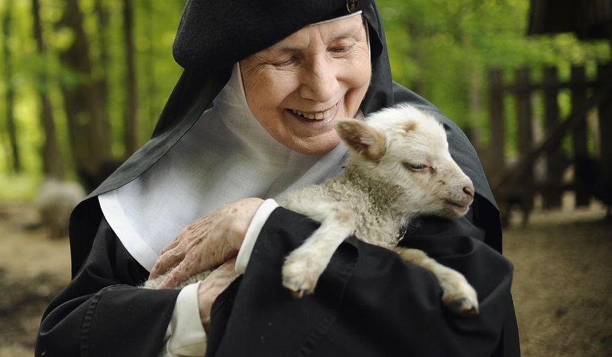 In this Friday, May 15, 2015 photo, Mother Dolores Hart holds a baby sheep at the Abbey of Regina Laudis, in Bethlehem, Conn. Mother Dolores, a former actress who is best known for sharing the first on-screen kiss with Elvis Presley, has helped the Abbey which is in need of renovations gain exposure and aid from fans of Presley. (AP Photo/Jessica Hill)