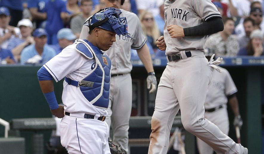 New York Yankees' Jacoby Ellsbury scores past Kansas City Royals catcher Salvador Perez on a sacrifice fly by Carlos Beltran during the third inning of a baseball game Saturday, May 16, 2015, in Kansas City, Mo. (AP Photo/Charlie Riedel)