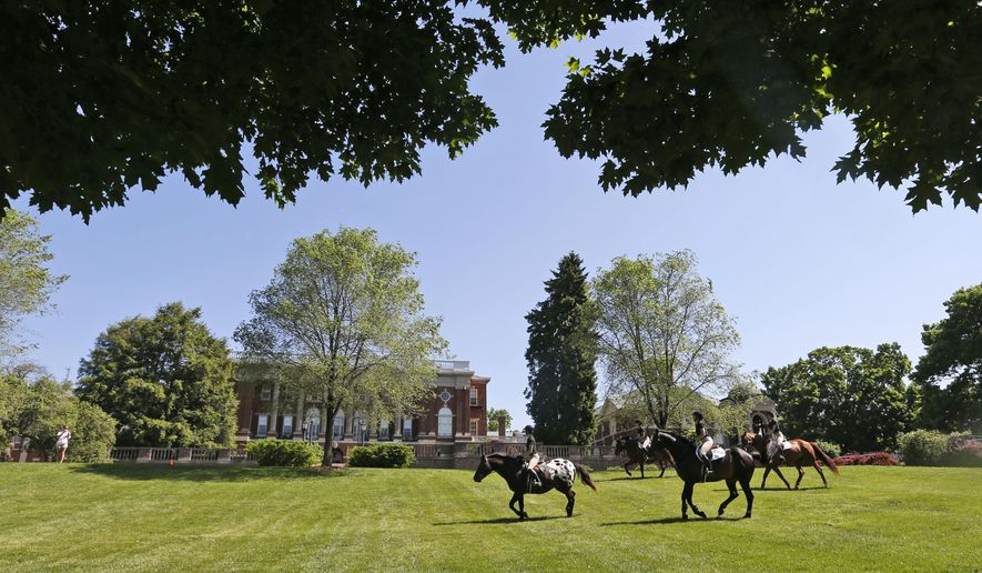 In this photo taken on Wednesday, May 13, 2015, graduating seniors at Sweet Briar college participate in the traditional senior ride on the quad at the school in Sweet Briar, Va.  The senior ride is a tradition where seniors are allowed to ride horses on school grounds. The school is scheduled to close in August with the final commencement ceremonies on Saturday May 16.   (AP Photo/Steve Helber)