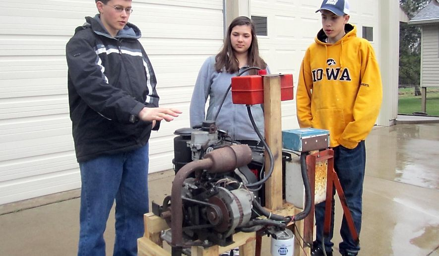 ADVANCE FOR USE MONDAY, MAY 18, 2015 - In this photo taken April 24, 2015, Brian Prchal, left, describes how the biodiesel engine he created compares to regular diesel in a one-cylinder engine in Montgomery, Minn., as Anna Prchal and Tyler Fromm look on. The students are participating in 4-H Science of Agriculture Challenge through the University of Minnesota Extension Service. (Nancy Madsen/The Free Press via AP)