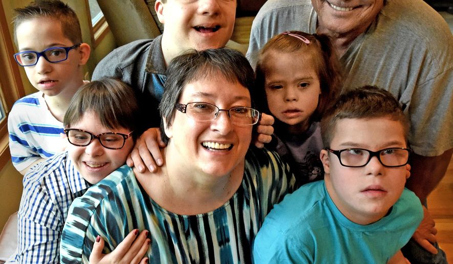 In this photo taken May 2, 2015, Leah Spring, center, poses with her familt at their home in Eagan, Minn. Spring blogs about raising five children with Down syndrome while fighting breast cancer. Surrounding her are, from left: Asher, 10, Angela, 18, Axel 14, Audrey, 10, husband Dean Ellingson and Abel, 12. (Jean Pieri/The St. Paul Pioneer Press via AP)  MINNEAPOLIS STAR TRIBUNE OUT