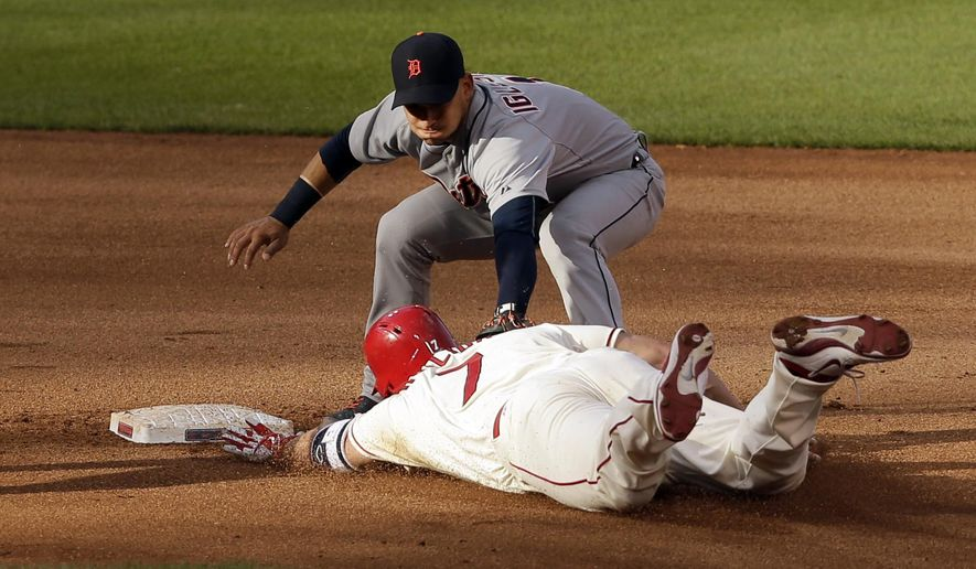 St. Louis Cardinals' Matt Holliday, bottom, is tagged out by Detroit Tigers shortstop Jose Iglesias while trying to stretch a single into a double during the 10th inning of a baseball game Saturday, May 16, 2015, in St. Louis. The Tigers won 4-3 in 10 innings. (AP Photo/Jeff Roberson)