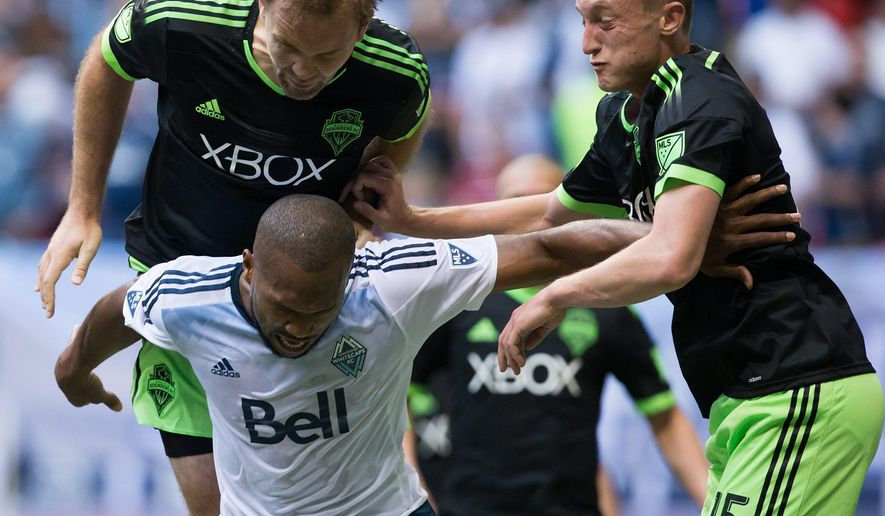 Seattle Sounders' Chad Marshall, top left, and Dylan Remick, right, defend against Vancouver Whitecaps' Kendall Waston, of Costa Rica, during the first half of an MLS soccer game in Vancouver, British Columbia, on Saturday, May 16, 2015. (Darryl Dyck/The Canadian Press via AP)