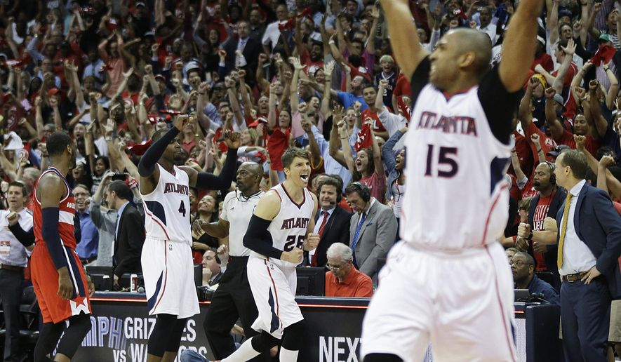 Atlanta Hawks' Kyle Korver, center, celebrates along with teammate Al Horford, right, as the Hawks beat the Washington Wizards 82-81 in Game 5 of the second round of the NBA basketball playoffs Wednesday, May 13, 2015, in Atlanta. (AP Photo/John Bazemore)