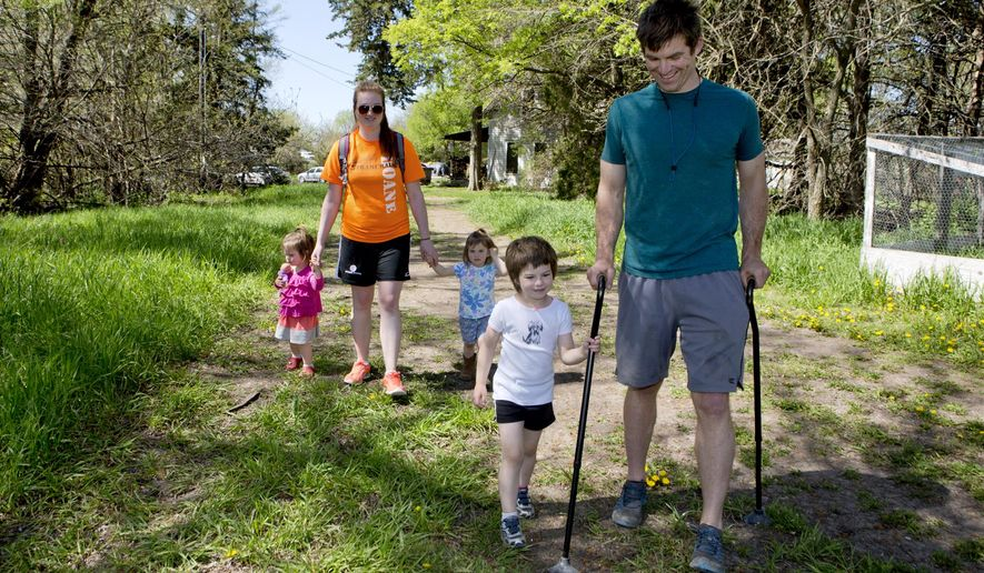 Nina McKiernan, center, 5, holds on to her father, Alex McKiernan's cane, as they walk back up to their Martell, Neb., home, followed by Nina's twin sisters, Fiona McKiernan, left, 2, and Roisin McKiernan, with their babysitter, Alyssa Hangman, 23, Thursday, April 30, 2015. McKiernan was rear-ended on Jan. 7, 2014, and suffered a spinal cord injury. Through rehabilitation at Madonna Rehabilitation Hospital he has regained the ability to walk with help from his canes.  (Kaylee Everly/The Journal-Star via AP) LOCAL TELEVISION OUT; KOLN-TV OUT; KGIN-TV OUT; KLKN-TV OUT