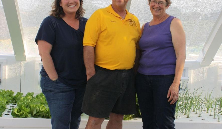 In this May 7, 2015 photo, Laura, Mark and Fran Krause pose for a photo in the greenhouse of their family business, Windy Drumlins, in Horicon, Wis. The family began their farm with the dream of being able to grow almost all of their own food and now it has expanded to become their business. (Bobbye Pyke/The Daily Citizen via AP)