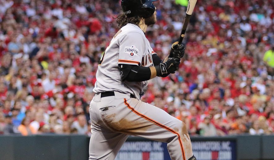 San Francisco Giants' Brandon Crawford ollows through on a grand slam off Cincinnati Reds' starting pitcher Mike Leake during the fifth inning of a baseball game Saturday, May 16, 2015, in Cincinnati. (AP Photo/Gary Landers)