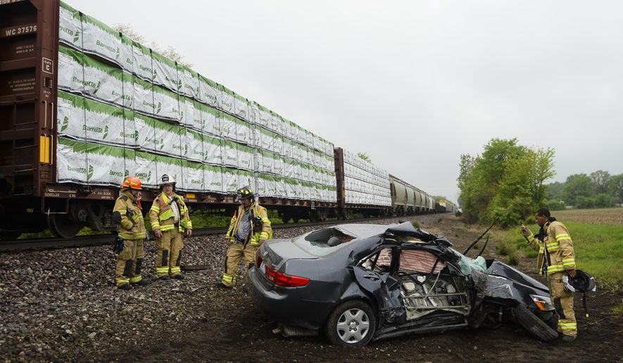 RETRANSMISSION TO CORRECT FROM WOMEN TO WOMAN - Firemen look at a car that was smashed by a train after it stalled traveling north on McKean Road in Augusta Township, Mich., on Saturday, May 16, 2015. The woman driving the Honda Accord was able to grab her purse and exit the car before it was hit. (Alex McDougall/The Ann Arbor News via AP) LOCAL TELEVISION OUT; LOCAL INTERNET OUT
