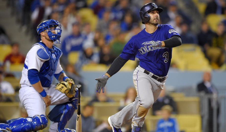 Colorado Rockies' Daniel Descalso watches his three-run double in front of Los Angeles Dodgers catcher Yasmani Grandal during the seventh inning of a baseball game, Friday, May 15, 2015, in Los Angeles. (AP Photo/Mark J. Terrill)