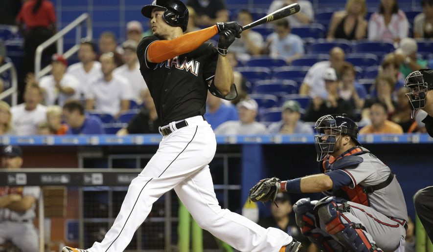 Miami Marlins' Giancarlo Stanton, left, follows through with a solo home run in the third inning of a baseball game against the Atlanta Braves, Saturday, May 16, 2015, in Miami. At right is Atlanta Braves catcher A.J. Pierzynski. (AP Photo/Lynne Sladky)