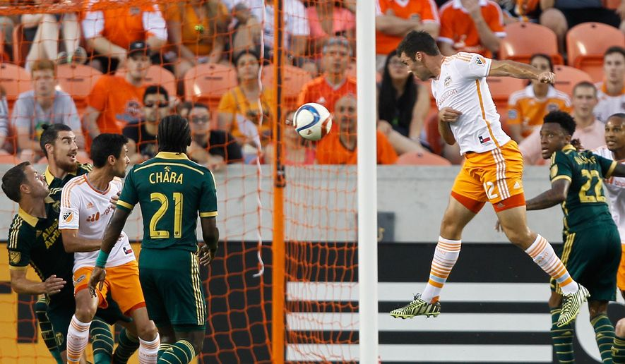 Houston Dynamo forward Will Bruin (12) scores on a header in the first half of an MLS soccer game against the Portland Timbers, Saturday, May 16, 2015, in Houston. (AP Photo/Bob Levey)