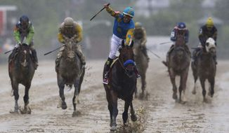 American Pharoah, ridden by Victor Espinoza, center, wins the 140th Preakness Stakes horse race at Pimlico Race Course, Saturday, May 16, 2015, in Baltimore. (AP Photo/Patrick Semansky)
