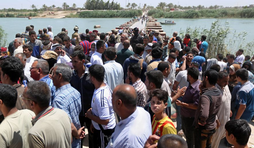Displaced Iraqis from Ramadi rest and gather at the Bzebiz bridge after spending the night walking toward Baghdad, as they flee their hometown, 65 km west of Baghdad, Iraq, Saturday, May 16, 2015. Islamic State militants seized the center of Ramadi in western Iraq and raised their black flag over the government compound, local officials said. (AP Photo/ Hadi Mizban)