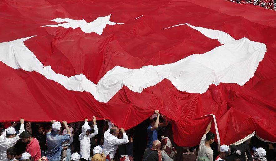 People carry a huge Turkish flag as Turkey's President Recep Tayyip Erdogan arrives to talk, during a local municipality event in Istanbul, Saturday, May 16, 2015. (Associated Press) ** FILE **