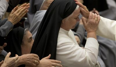 Pope Francis blesses a nun as he arrives for an audience with clergy of Roman archdiocese in the Paul VI hall at the Vatican, Saturday, May 16, 2015. (AP Photo/Alessandra Tarantino)