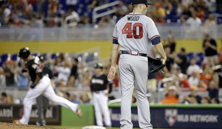 Atlanta Braves starting pitcher Alex Wood (40) stands on the mound as Miami Marlins' Giancarlo Stanton, left, rounds the bases after hitting a solo home run in the third inning of a baseball game, Saturday, May 16, 2015, in Miami.  (AP Photo/Lynne Sladky)