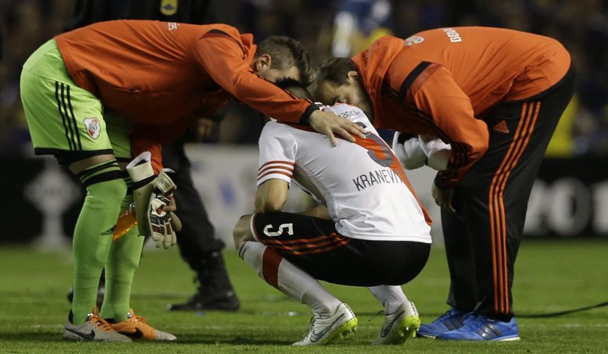 Matias Kranevitter of River Plate talks to his team's staff after he and his fellow players were affected by an unknown substance before the start of the second half of a Copa Libertadores soccer match with Boca Juniors in Buenos Aires, Argentina, Thursday, May 14, 2015. The match between the bitter the Argentine rivals was suspended after River Plate players were sprayed with a substance that seemed to affect their vision and irritated their eyes. (AP Photo/Natacha Pisarenko)